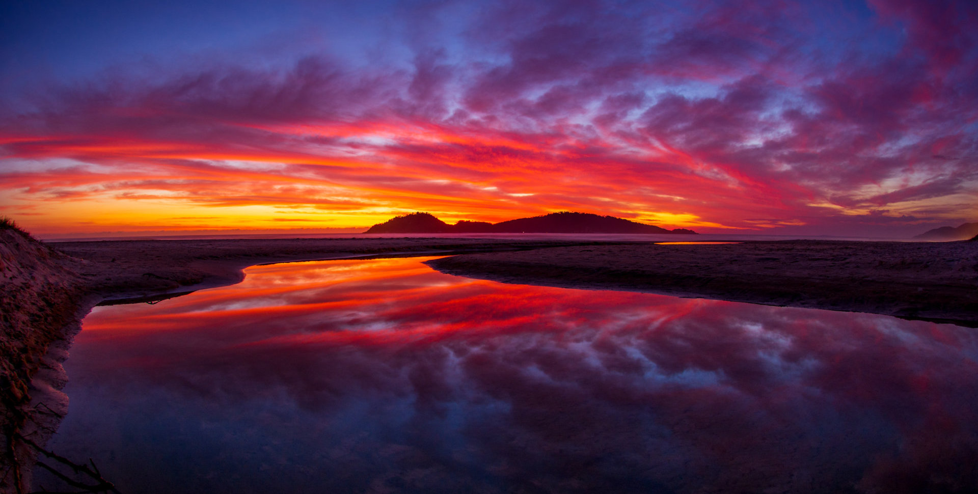 amazing sunrise with red, orange and yellow clouds and reflection on the water