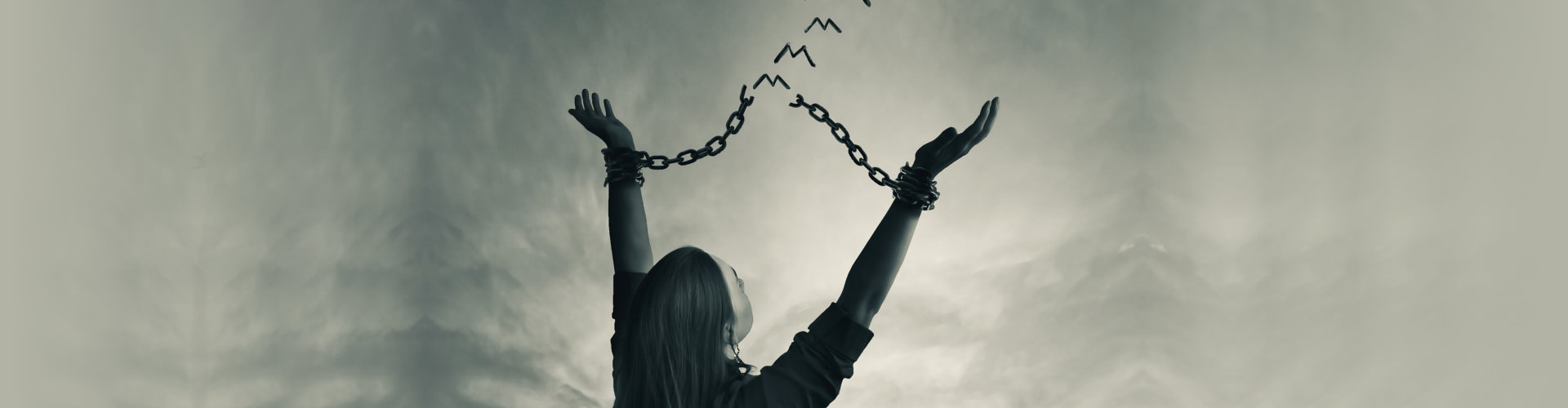 A woman breaks her chains as the links turn into freedom birds